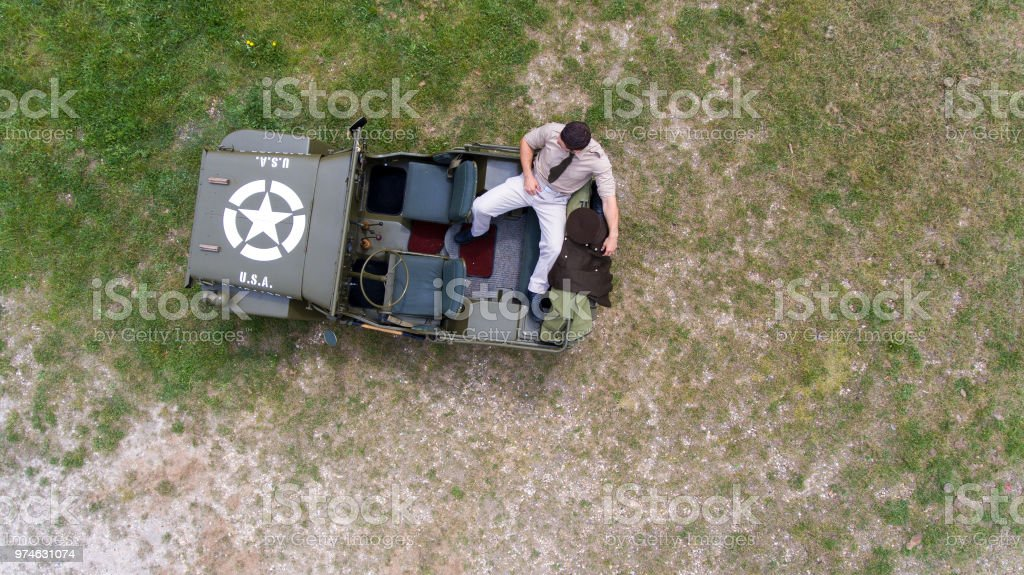 Overhead, drone, looking down on Male army officer in uniform resting on back of military vehicle stock photo