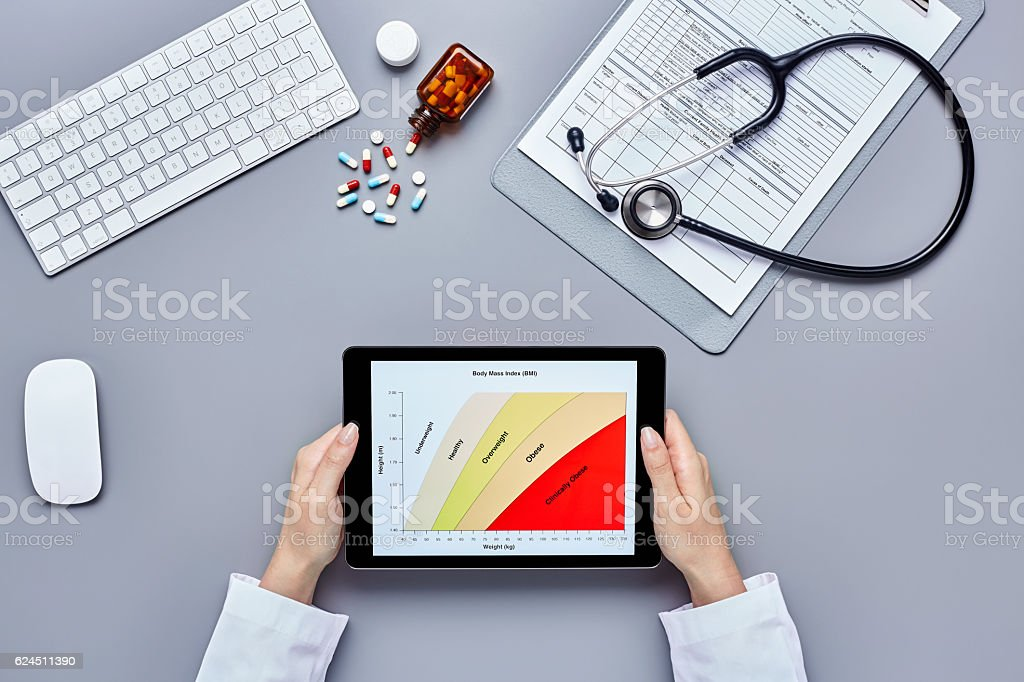 Overhead female doctor analyzing body mass index on digital tabl stock photo