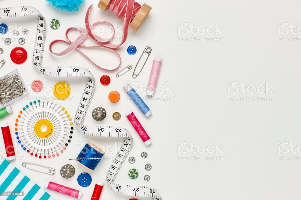Overhead flat lay of colorful sewing equipment on white background