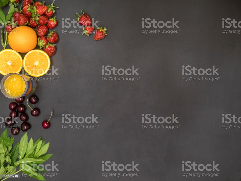 overhead flat lay of fresh raw mint cherry orange juice glass and strawberry with copy space mockup stock photo