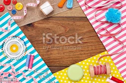 istock Overhead flat lay of sewing items and textiles on wood 849210734