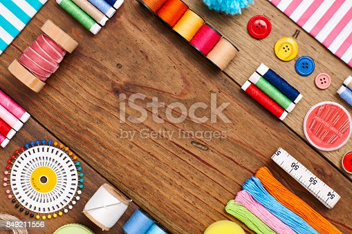 istock Overhead flat lay of sewing items arranged on wood 849211556