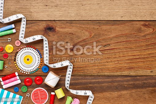 istock Overhead flat lay of sewing items in corner of table 849211884