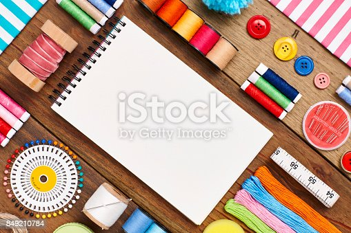 istock Overhead flat lay of spiral notebook with sewing items 849210784