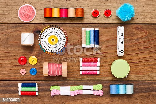 istock Overhead flat lay of various sewing items arranged on wood 849208672