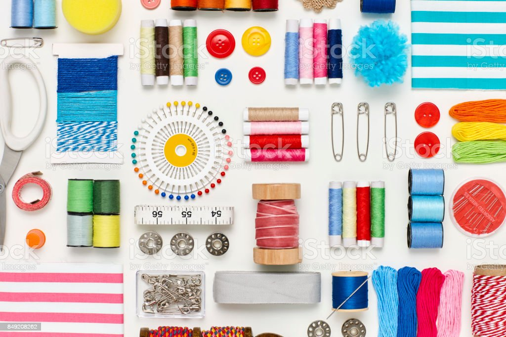 Overhead flat lay of various sewing items on white background