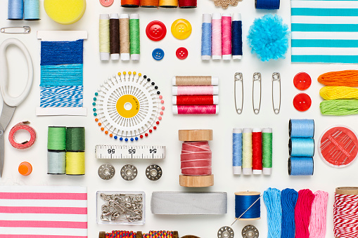 Flat lay of various sewing items on white background. Overhead view of art and craft products arranged side by side. Multi colored craft materials representing creativity.