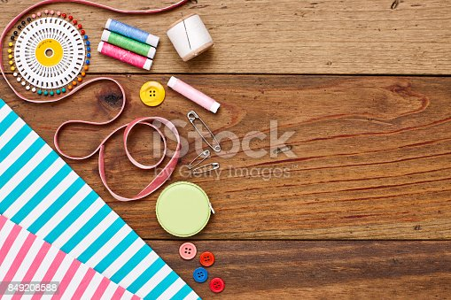 istock Overhead flat lay sewing equipment and striped fabrics of table 849208588