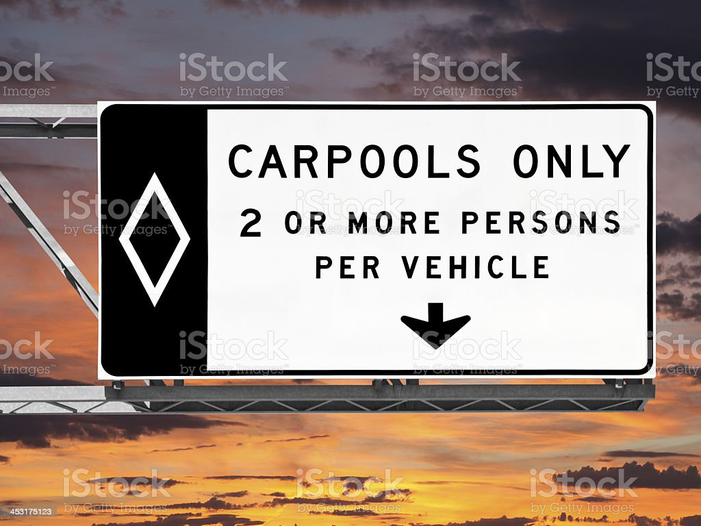 Overhead Freeway Carpool Only Sign with Sunset Sky stock photo