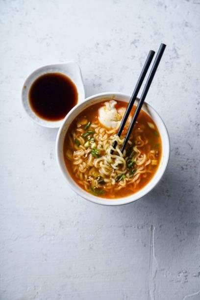 obenliegende bild einfach japanische ramen mit nudeln, schweinefleisch brühe, ei und lauch in schüssel auf konkrete hintergrund weiß - schnelle suppen stock-fotos und bilder