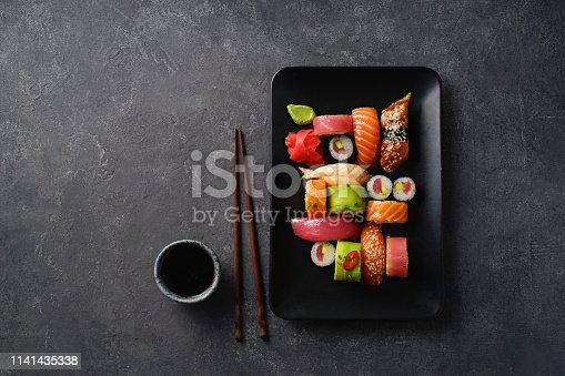 istock Overhead image of variety of sushi and rolls served on a plate. Shrimp, unagi, crab, salmon and tuna 1141435338