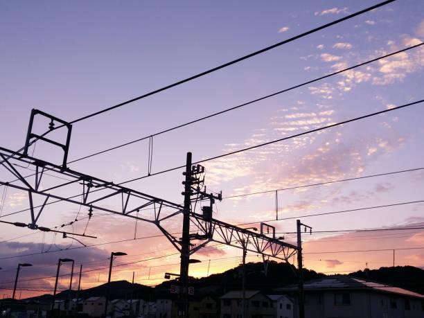 電車と夕暮れ時に空の頭上式ラインは。 ストックフォト