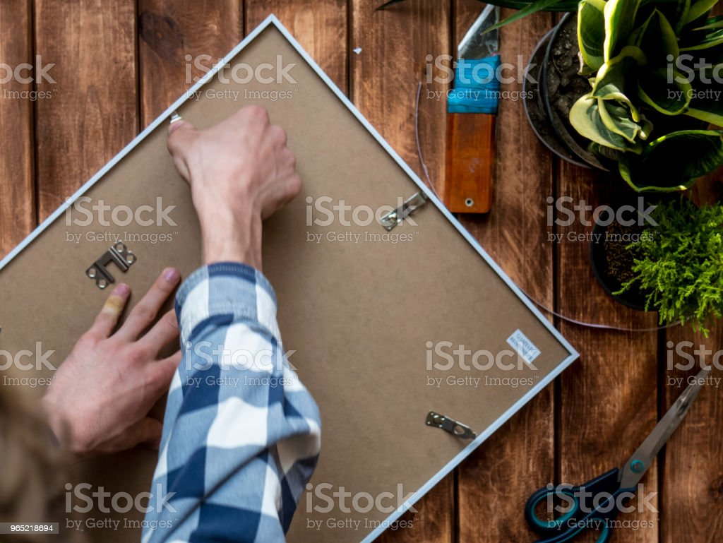 overhead man putting a photo in a wooden frame zbiór zdjęć royalty-free