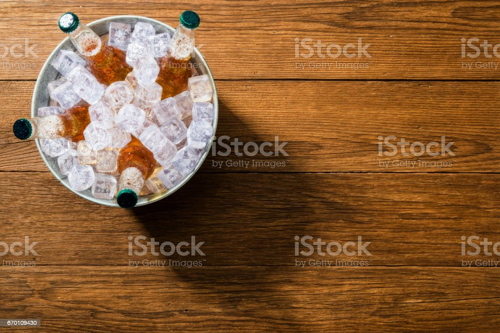 Sobrecarga de um balde de garrafa de cerveja gelada de gelo em pranchas de madeira - foto de acervo