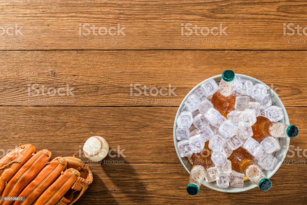 Overhead of a bucket of ice cold beer with baseball and glove on wood planks stock photo