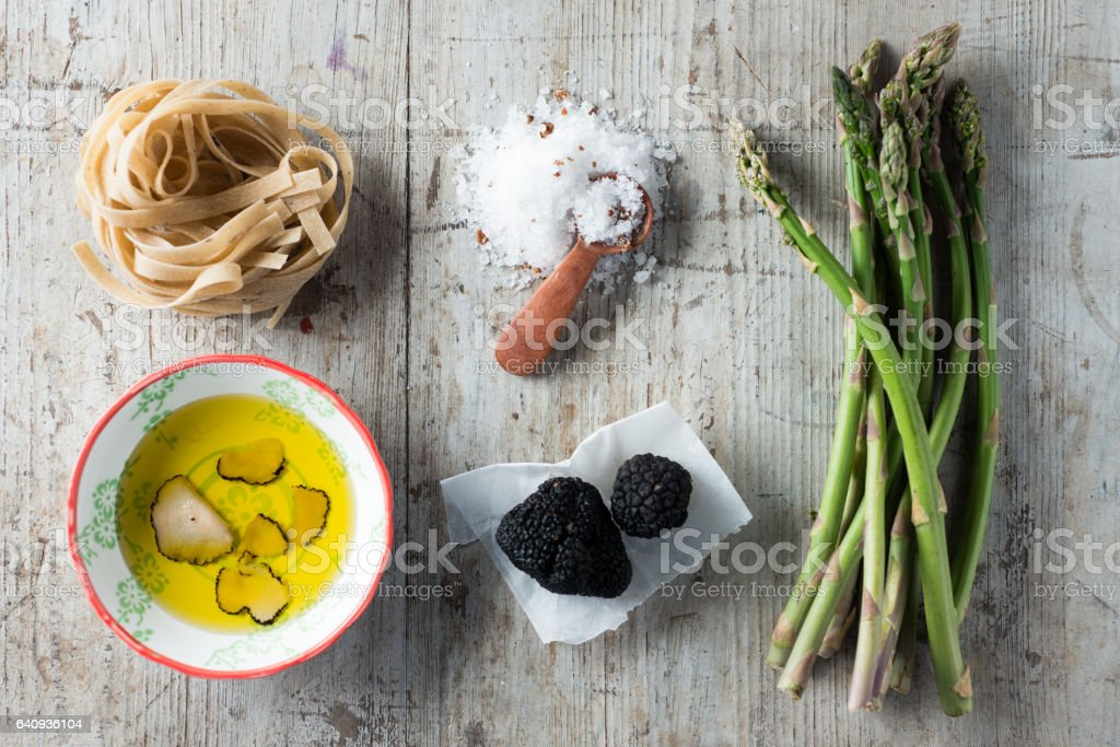 Overhead of Cooking Ingredients Including Black Truffles, Pasta, and Asparagus stock photo