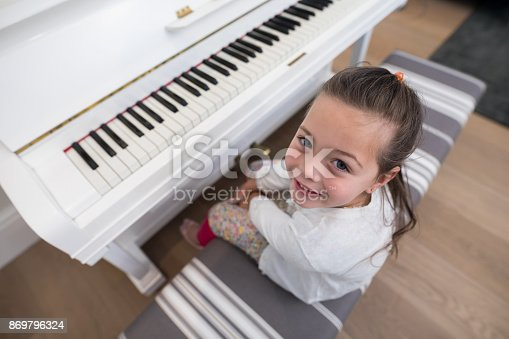 istock Overhead of cute girl playing piano 869796324