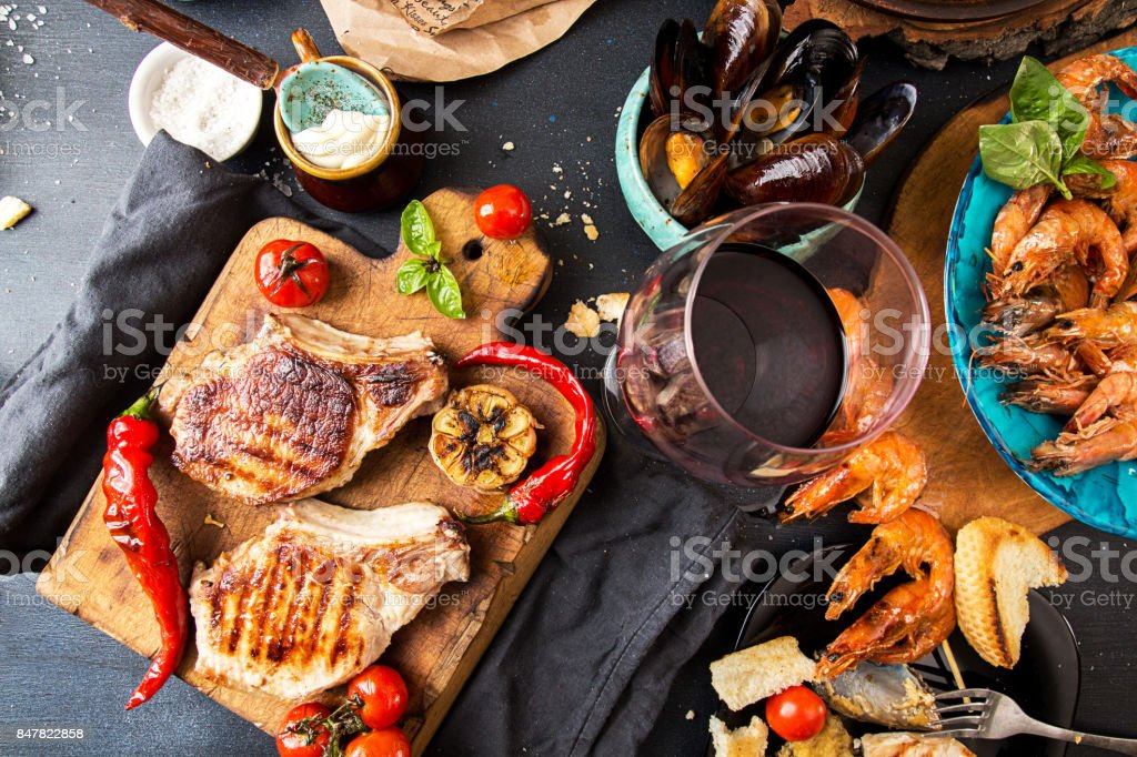 Overhead of dinner table. Assorted delicious grilled barbecue meat and seafood with vegetable. Pork grilled steaks, grilled baked mussels, shrimps, cherry tomato, chilii pepper, glass of red wine. Picnic bbq party concept. stock photo