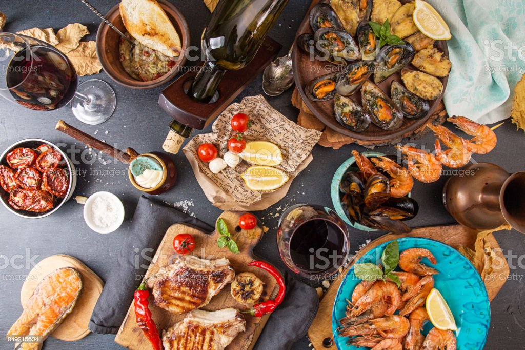 Overhead of dinner table. Assorted delicious grilled barbecue meat and seafood with vegetable. Pork grilled steaks, grilled salmon trout, mussels, shrimps, dried tomato, cherry tomato, chilii pepper, glass of red vine. Picnic bbq party concept stock photo