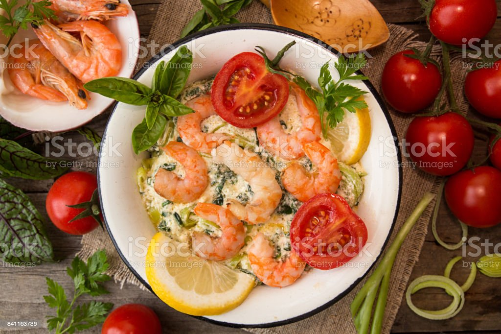 Overhead of dinner table. Seefood casserole with leek, cheese, grilled shrimps, serving with tomato cherry, parsley and basil. Ingredients around plate with seefood meal on old wooden background. Healthy diet seafood concept. stock photo