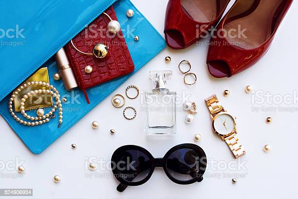 Fashionable female accessories watch sunglasses lipstick blue clutch and red shoes . Overhead of essentials for stylish young woman.