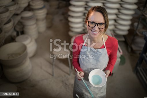 istock Overhead of female potter painting bowl 856076090