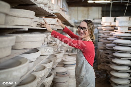 istock Overhead of female potter painting bowl 856076116