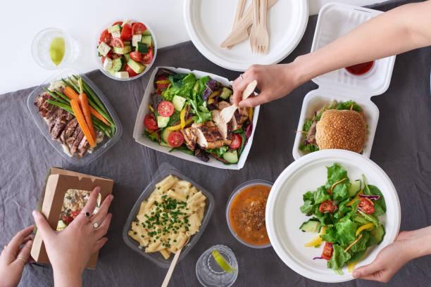 overhead of hands dishing up helpings of takeaway foods - food delivery стоковые фото и изображения