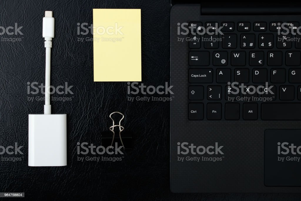 Overhead of office table with laptop, computer keyboard and sticky notepad, port adapter royalty-free stock photo