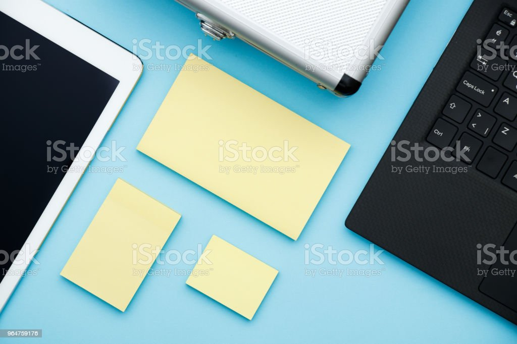 Overhead of office table with laptop, computer keyboard, tablet pc and sticky notes, pencil. copy space flat lay royalty-free stock photo