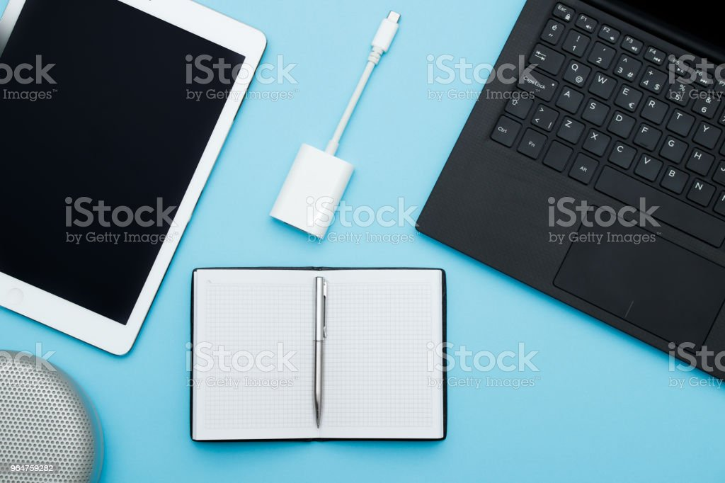 Overhead of office table with laptop, computer keyboard, tablet pc and notebook, speaker, ports adapter, pencil. flat lay royalty-free stock photo