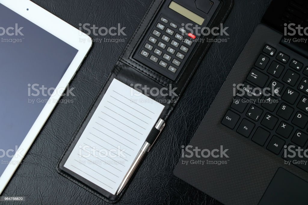 Overhead of office table with notebook, computer keyboard, tablet pc, calculator, notepad copy space, pencil. royalty-free stock photo