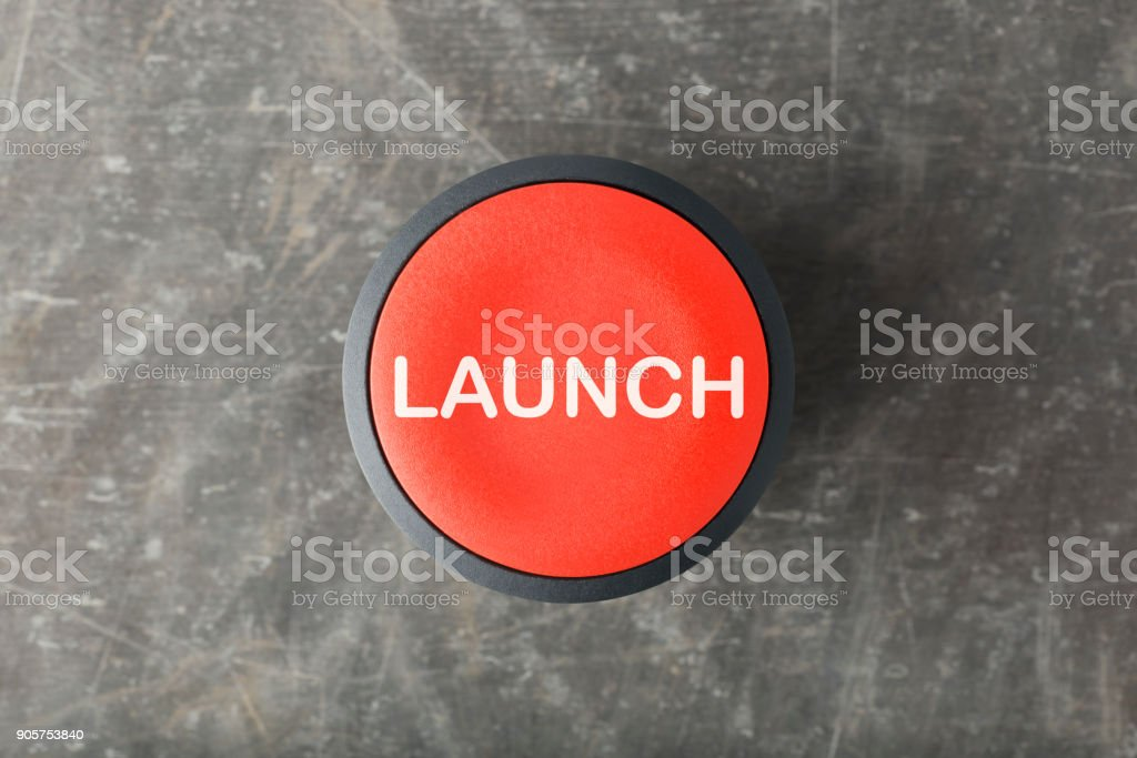 Overhead of Red 'Launch' Push Button on Concrete Background stock photo