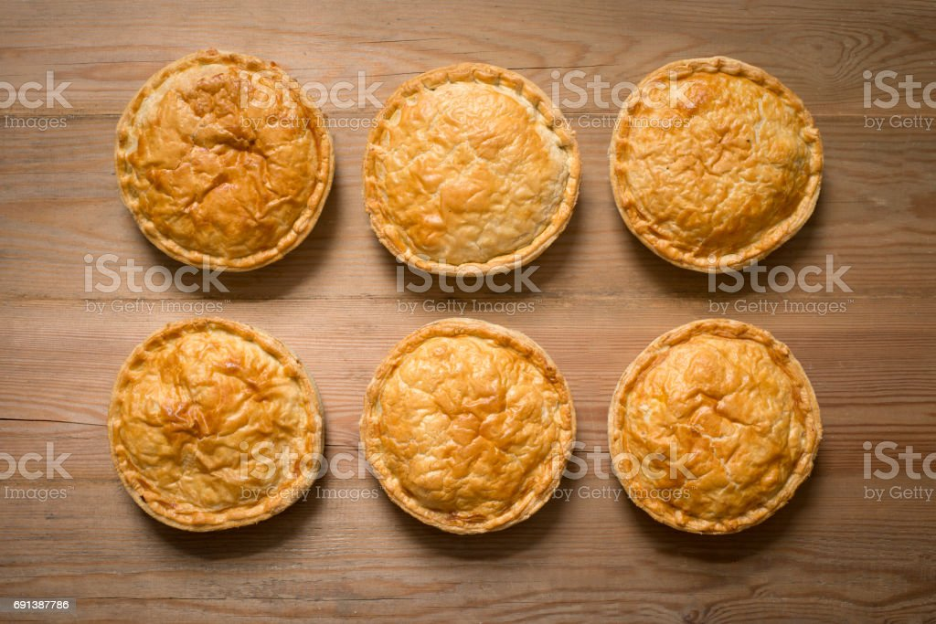 Overhead of Six Cooked Whole Pies on Wooden Surface stock photo