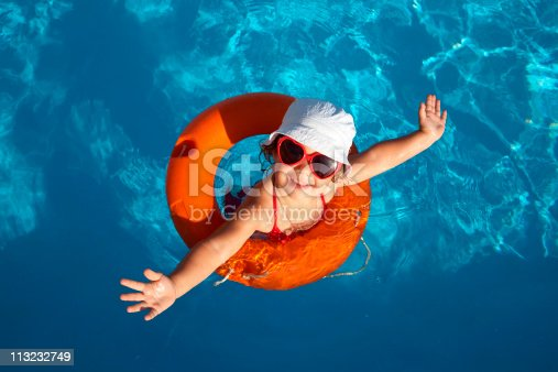 istock Overhead of young girl in orange life preserver 113232749