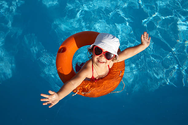 overhead of young girl in orange life preserver - swimmingpool kids stockfoto's en -beelden