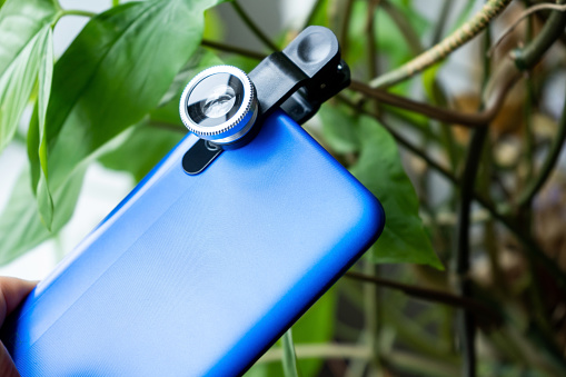 Overhead phone lens with clips on the blue modern smartphone. Extra macro camera for mobile device