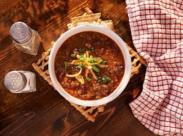 overhead photo of a bowl of chili overhead photo of a bowl of chili with cheese and green onions chili con carne stock pictures, royalty-free photos & images