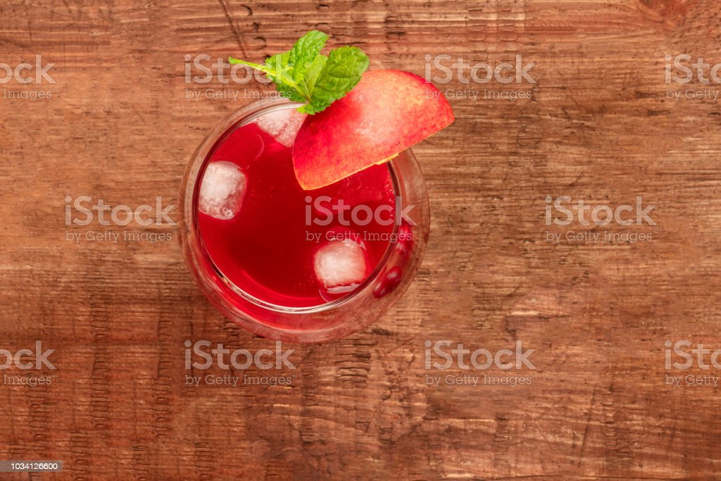 Overhead photo of a vibrant red drink with berries on a rustic background stock photo