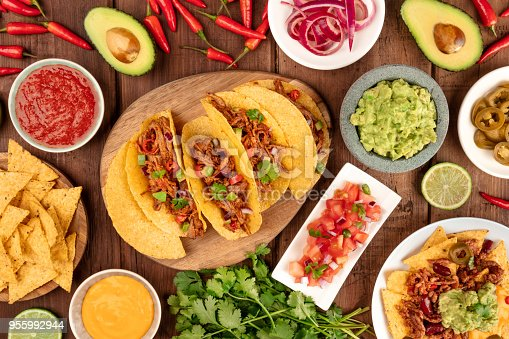 An overhead photo of an ssortment of many different Mexican tapas, including tacos, guacamole, pico de gallo, nachos and others