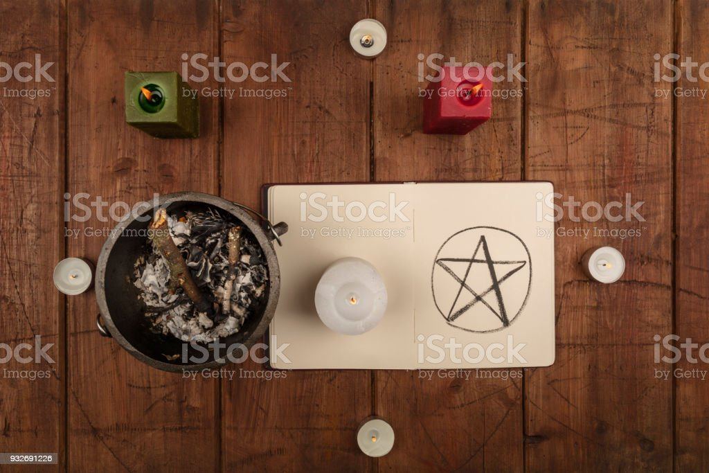 Overhead photo of cauldron, grimoire, and candles stock photo