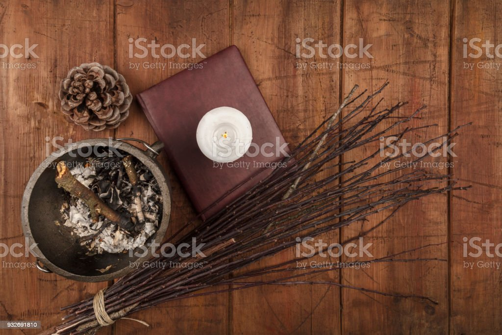 Overhead photo of cauldron, grimoire, candle, and a broom stock photo