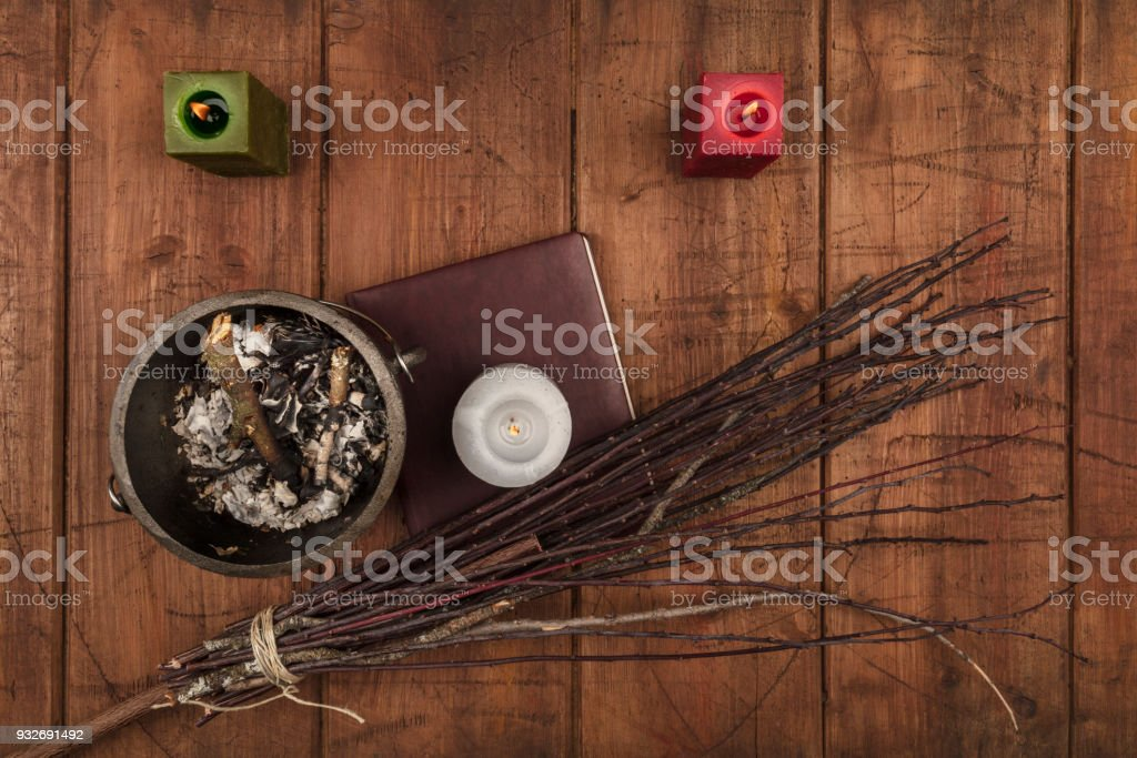 Overhead photo of cauldron, grimoire, candles, and a broom stock photo
