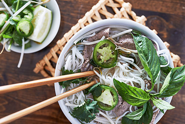 overhead photo of eating vietnamese beef pho - pho soup stock photos and pictures