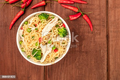 An overhead photo of a bowl of noodles with chicken, green peas, and broccoli, with red hot chili peppers and copy space, on a dark rustic background texture