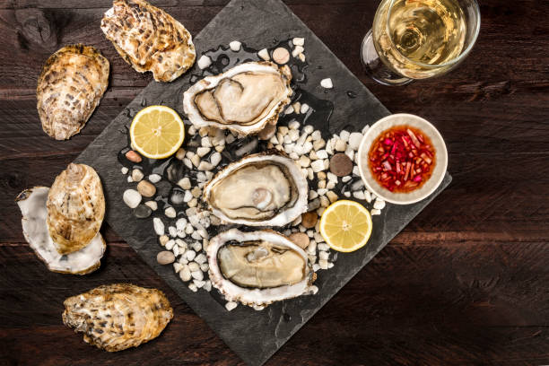 Overhead photo of oysters with wine, lemon, and vinaigrette sauce An overhead photo of freshly opened oysters on ice, with a glass of white wine, lemon slices, vinaigrette sauce, and copy space, on dark textures vinaigrette dressing stock pictures, royalty-free photos & images