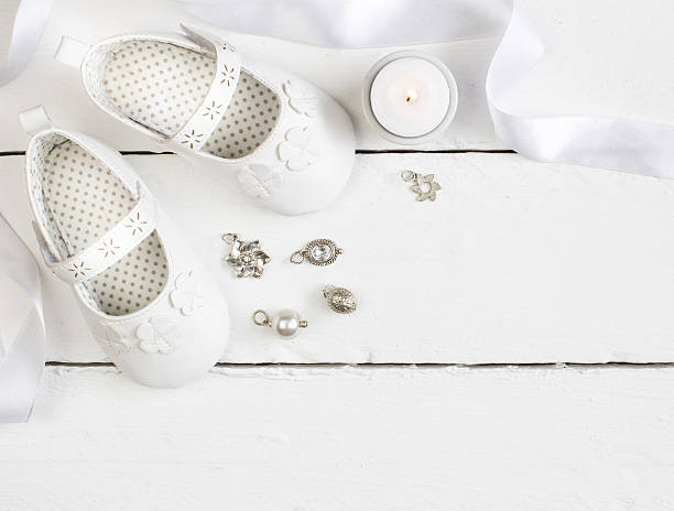 overhead photo of pair of white baby booties, candle, ribbon - batizado - fotografias e filmes do acervo