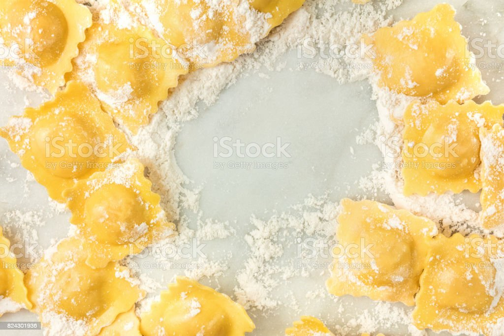 Overhead photo of ravioli with flour and copy space stock photo