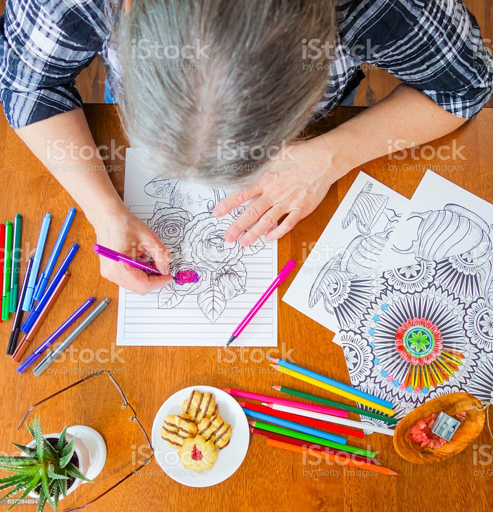 Overhead Photo of Senior Woman Holding Pink Marker Coloring Flowers stock photo
