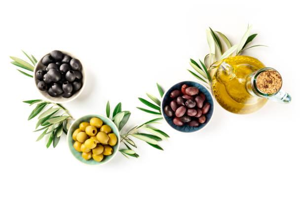 Arriba foto de diferentes aceitunas en tazones de fuente y una Alcuza de aceite de oliva, un disparo desde la parte superior sobre un fondo blanco con espacio de copia - foto de stock
